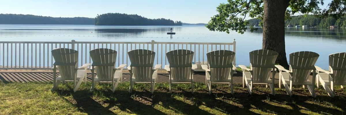 A row of white, Muskoka chairs sit on the shore of Lake Joe.