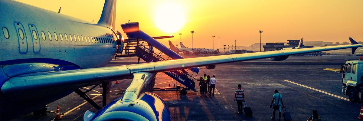 People boarding an airplane at sunset.