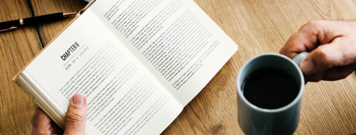 close up of hands holding a book and a coffee cup