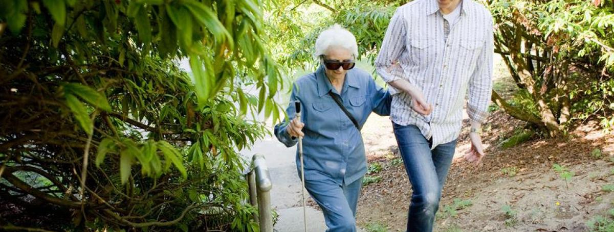 sighted guide walking with a woman using a white cane