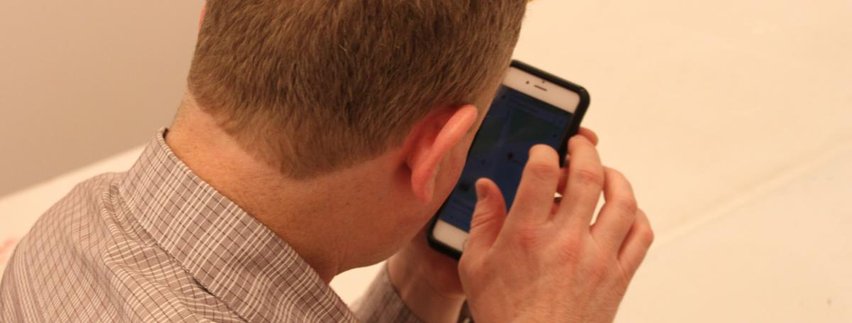 An over the shoulder shot of a man holding his iPhone using voiceover.