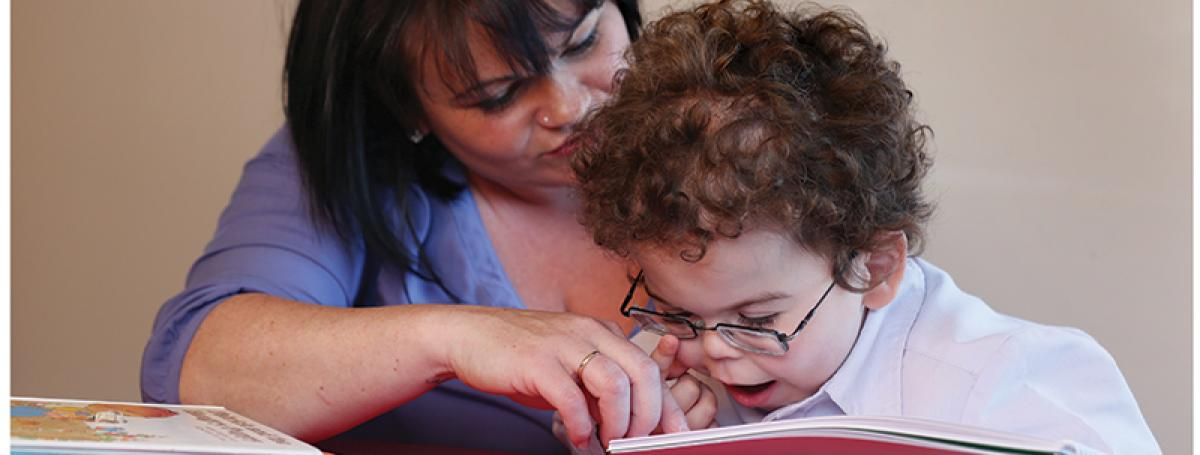 A young boy reads a tactile book. His mother helps guide his hands over the book.