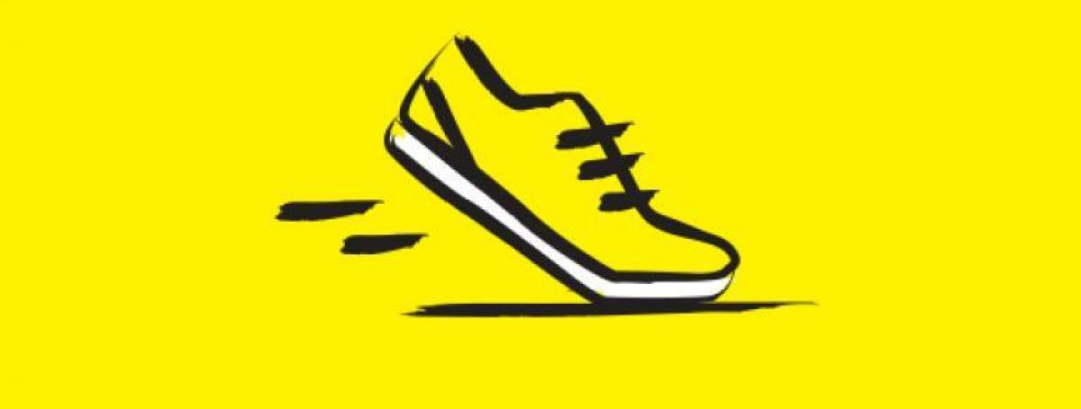 An illustration of a running shoe outlined in thick, black, paintbrush design.