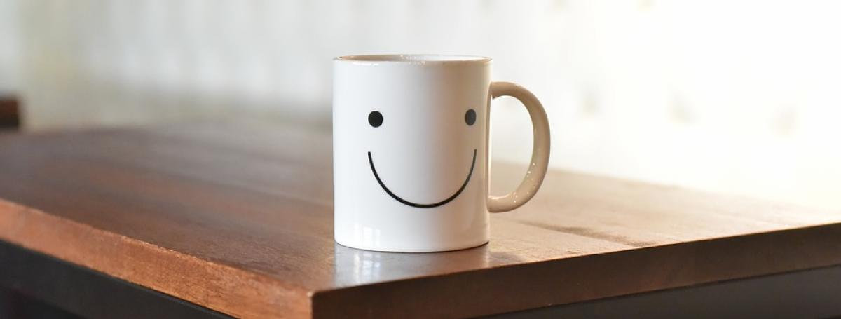 White mug sitting on a wood table. The mug has a smiley face on it.