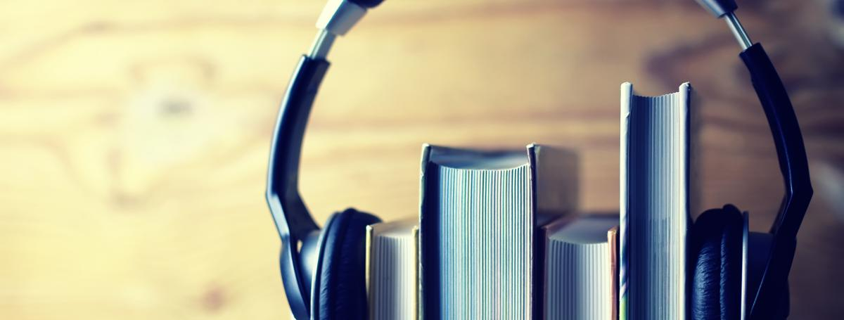 A stack of four books sits on a shelf. A pair of headphones sits on top of the books - holding them together.