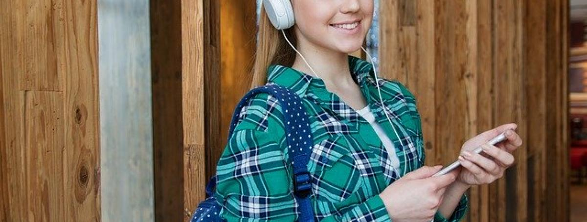 A teenage girl wears headphones connected to her iPhone and smiles at the camera.