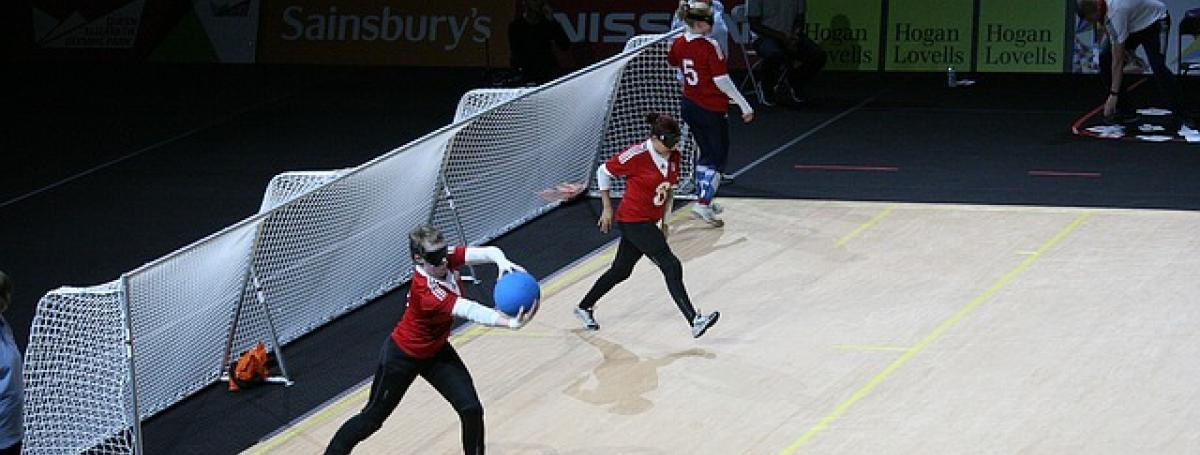 Three people practicing goalball guarding nets.