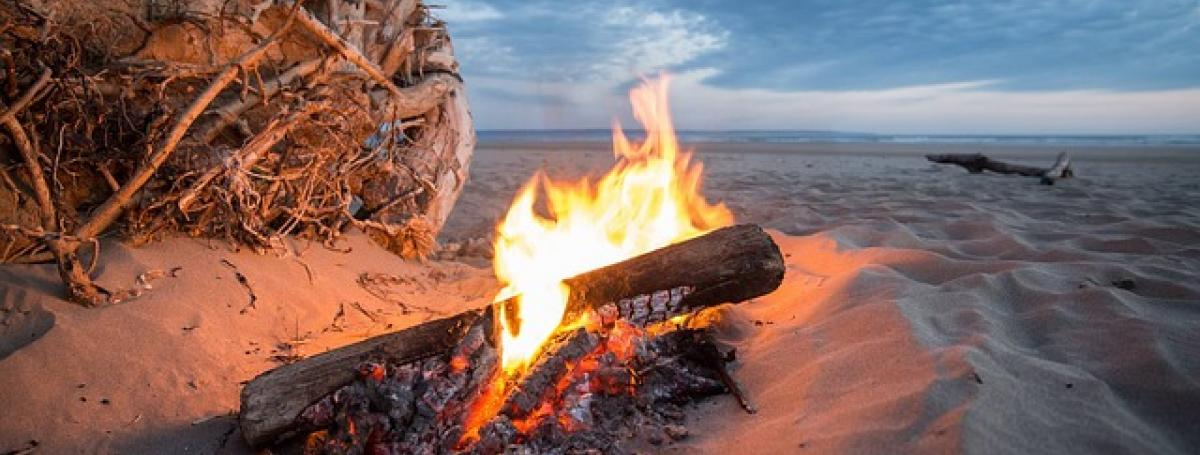 A campfire on a sandy beach.