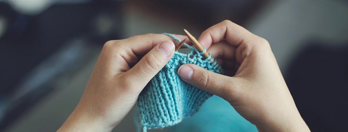 Two hands hold knitting needles and knit a blue fabric.