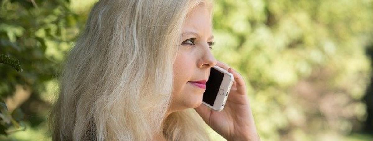A woman holds an iPhone to her ear and listens intently to a private conversation.