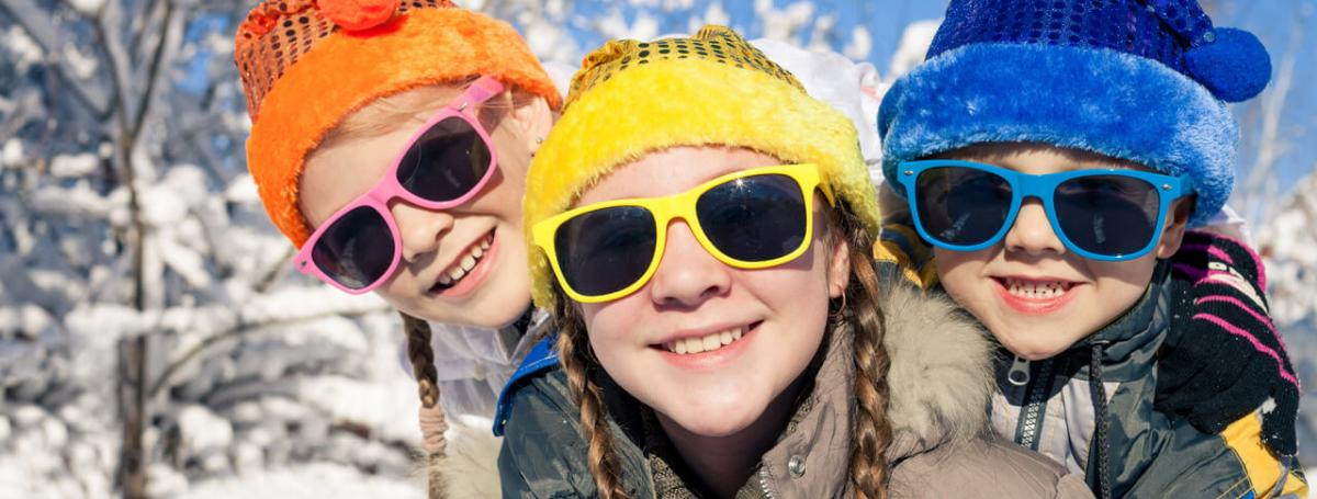 Three children outside in the snow wearing colourful hats and sunglasses