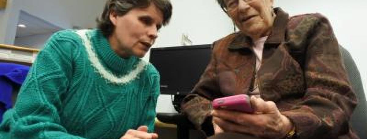 A technology training workshop. One woman teaches another elderly woman how to use her iPhone.