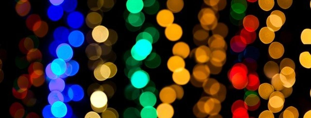 An abstract design of glittering rainbow-coloured christmas tree lights.