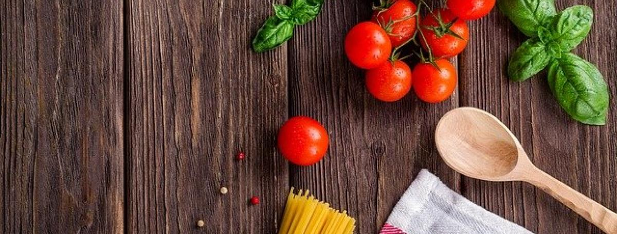A cutting board. A wooden spoon, basil, tomatoes and pasta sit on top of the board.