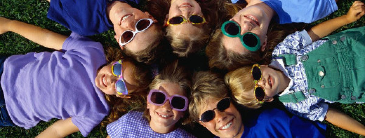A circle of children laying on the grass looking up. They are all smiling with colourful sunglasses.