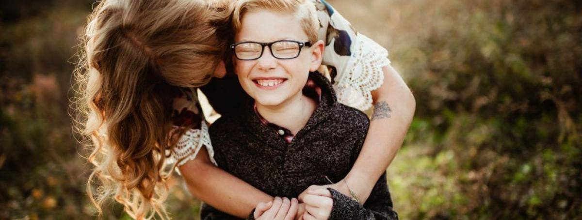 Woman hugging boy wearing glasses outdoors.
