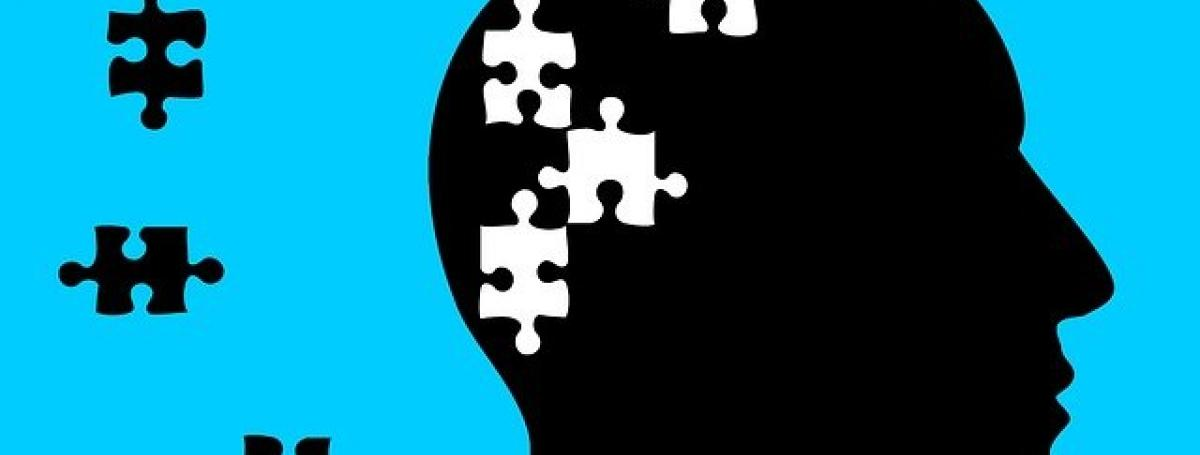 A blue and black illustration of the profile of a bald man. Inside his head are missing puzzle pieces. Juxtaposed to the illustration of his head are the puzzle pieces sitting in the wallpaper frame.