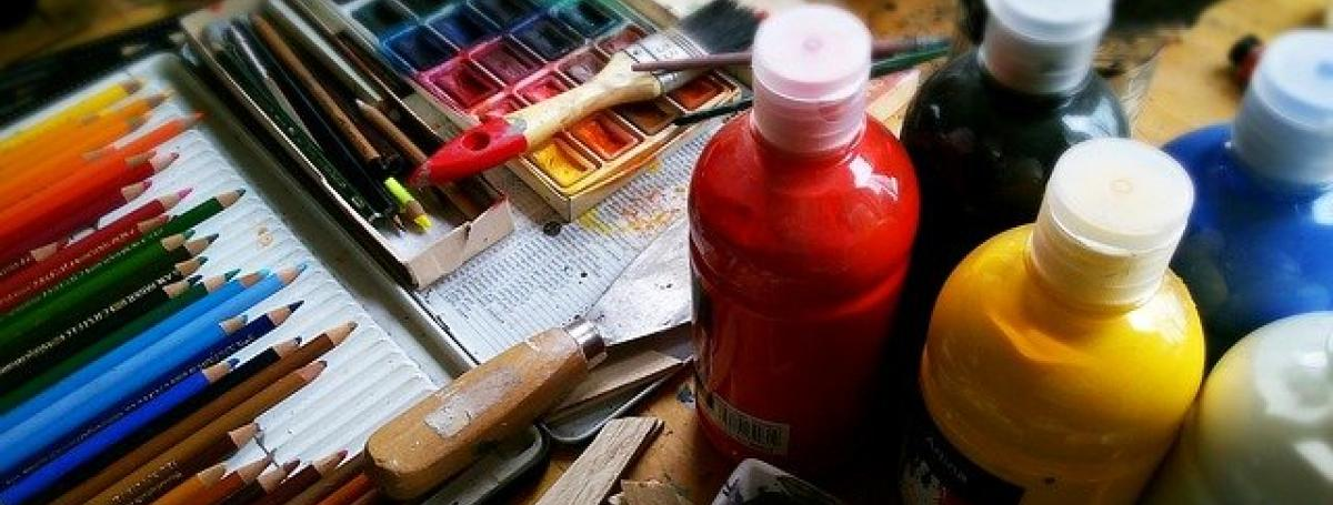 A tabletop covered in art supplies; coloured pencils, paintbrushes and jugs of paint.