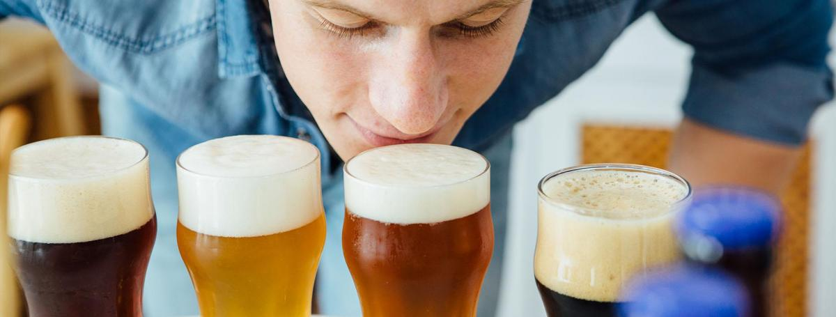 Man bending over to sniff one of four full glasses of beer.