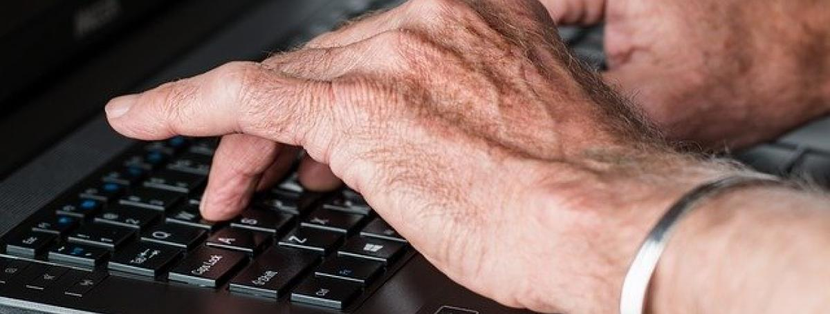 Two hands type on a laptop keyboard.