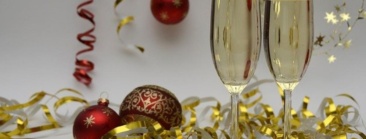Two glasses of champagne sit on a table which is littered with Christmas bulbs, glitter and ribbon.