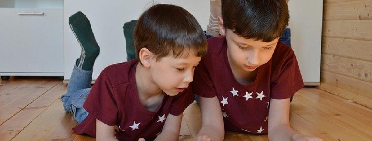 Two young brothers sit on their bedroom floor and interact with an iPad.