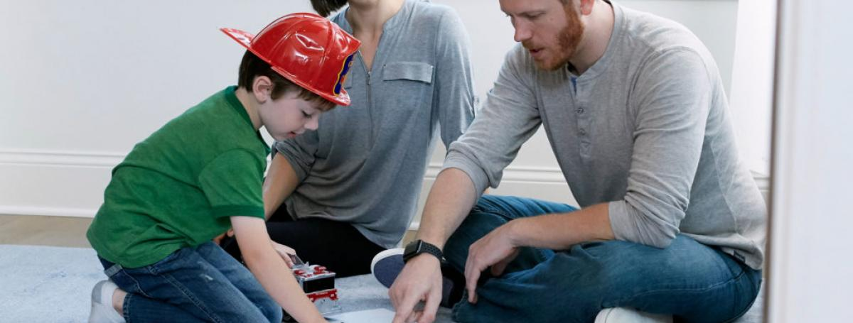 A family sits on the floor looking at a floor plan. There is a red fire extinguisher on the floor and the boy is wearing a firefighter hat.