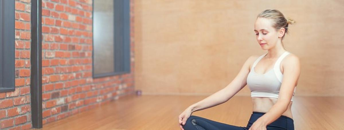 A woman sits on a yoga mat and meditates.