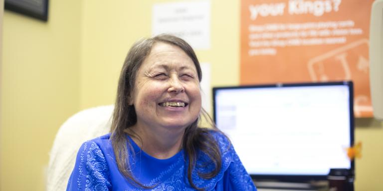 Woman sitting in a chair, smiling. Behind her is a computer screen and an orange poster on a yellow wall.