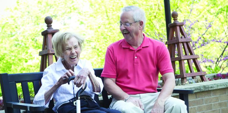 An older woman and man sitting on a bench laughing