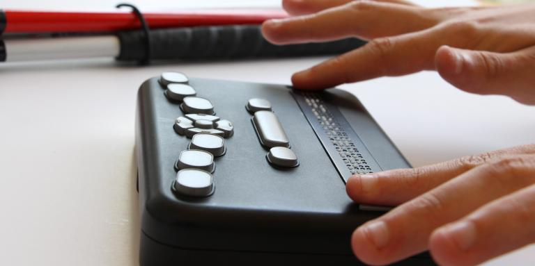 Hands reading the Orbit Braille Reader with a white cane in the background