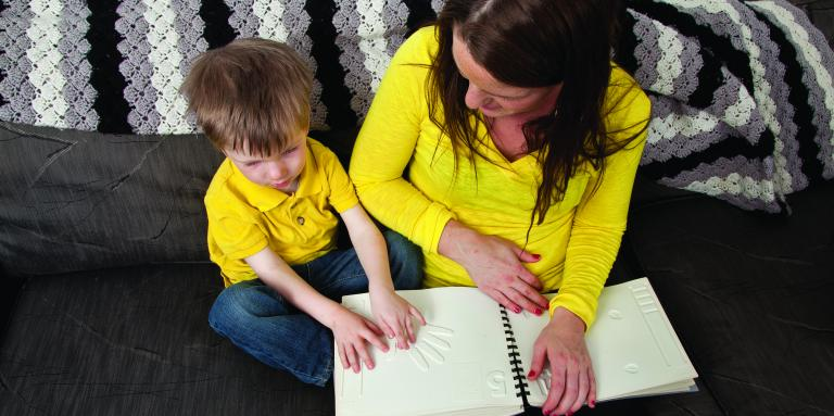 A little boy sits next to his mother on a couch reading a tactile book. Both are in yellow shirts.