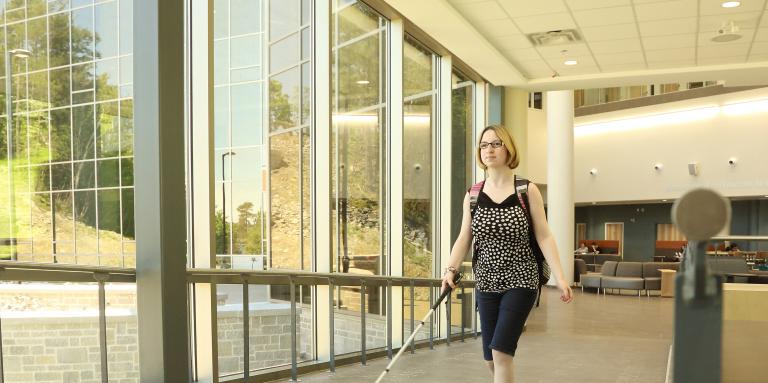 A young blond woman walking down a hallway with her white cane