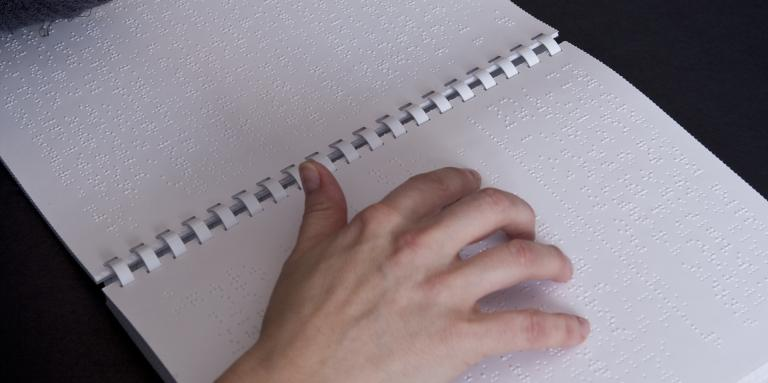 a woman reads a braille book.