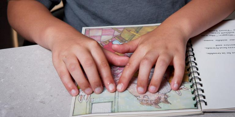 Boy reading a children's braille book