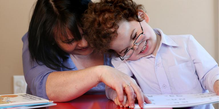 Mother and son reading a braille book