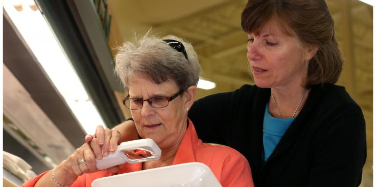 Older female holds a magnifier to a package. She is standing in front of another woman who is helping her with the magnifier.