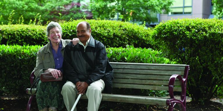Man with white cane and woman sitting together on bench