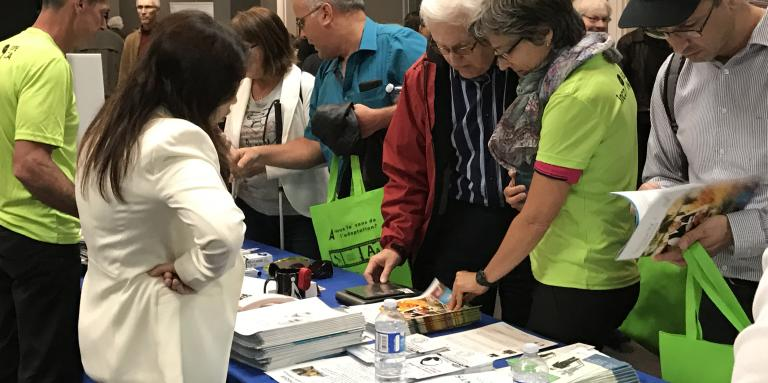 Visitors looking through pamphlets at an exhibitor table