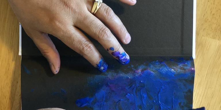 Close up of Neena's hands painting in blue on her sketch pad.