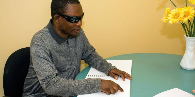 Man with sunglasses reading braille