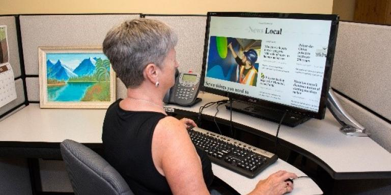 a woman sits at a computer using Zoomtext.