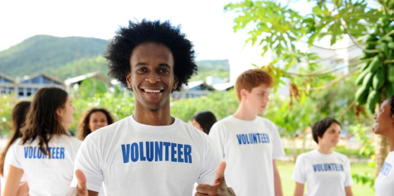 Man wearing Volunteer T-shirt and giving thumbs up sign