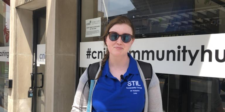 Hillary Scanlon stands in front of a CNIB community hub wearing the shirt with her brand on it: Sustainability Through an Inclusive Lens.