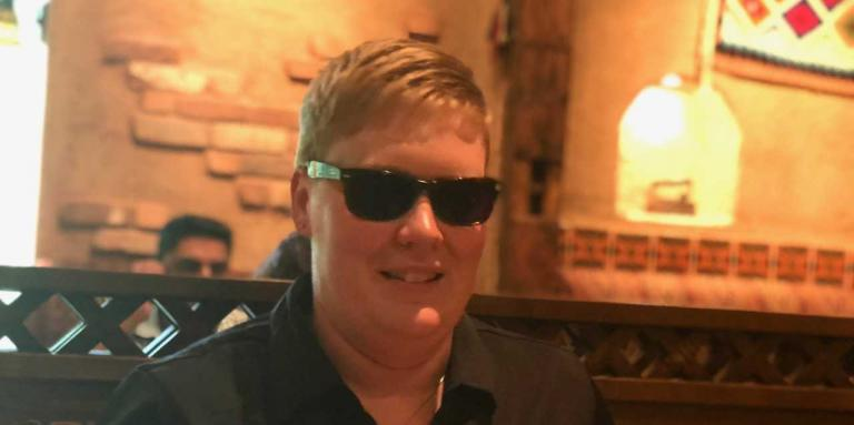 Ashley Nemeth smiles and sits in a restaurant, wearing sunglasses.