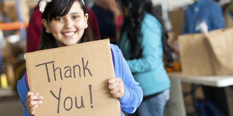 Smiling young girl holding handwritten Thank You sign