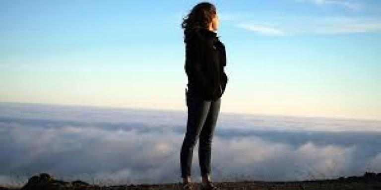 A woman stands on top of a mountain, looking out over the clouds and ground below. Her hair blows in the breeze and the sky is bright blue.