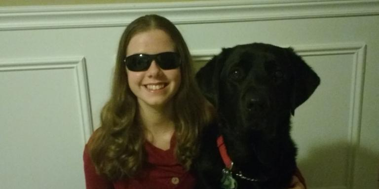 Teen girl with sight loss smiling and wrapping arm around her guide dog