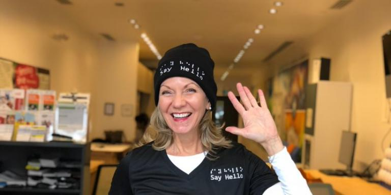 Denise Justin smiles and waves, wearing a shirt and toque with the Say Hello logo. She's standing in a CNIB hub in Toronto.