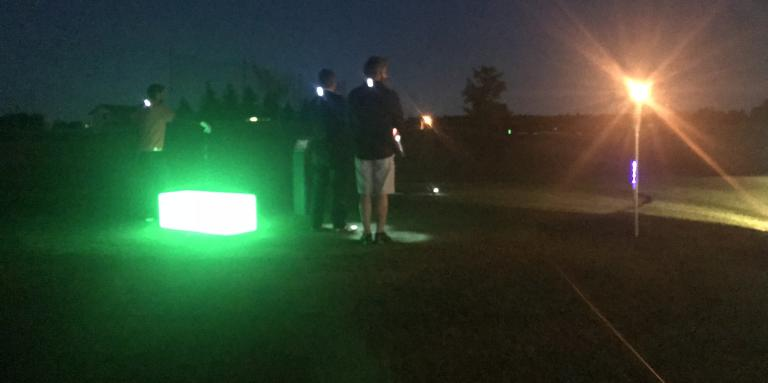 Golfers standing on the green with lights around themGolfeurs sur le vert entourés de lumières.